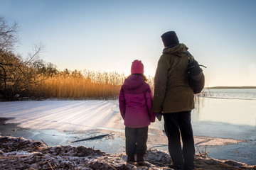 Woman and young girl looking at beautiful winter sunset against icy water and blue sky, late afternoon.