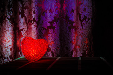 Valentine's Day composition with sweet burning multicolored heart on dark background, selective focus, or love greeting card of heart red green pink yellow