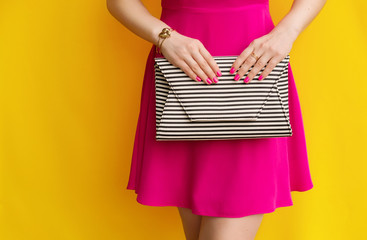 Wall Mural - fashionable girl in pink dress with striped handbag