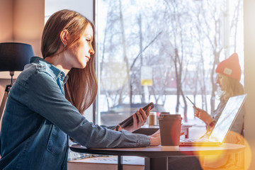 Sunny day.Side view of young business woman in denim jacket sits at table in cafe and using laptop while holding smartphone.On table cup of coffee. In background girl sitting near window and chatting.