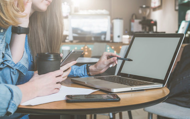 Two young business women sitting at table in cafe, drinking coffee and talking. First woman holding pen and smartphone.On table laptop and cup of coffee. Students learn online. Meeting of two friends.