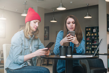 Teamwork. Two young businesswomen sitting at table in coffe shop, look at your smartphone screen and discuss business strategy. Girl taking notes in notebook. On table laptop and cup of coffe.