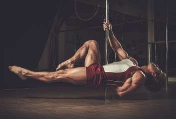 Handsome man performing pole dance moves on pole Wall mural