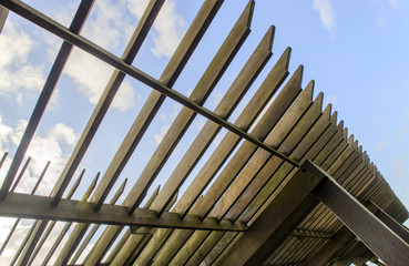 close-up of a wooden garden pergola with the blue sky in the background