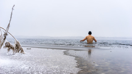 Junger Mann mit Mütze geht Eisbaden