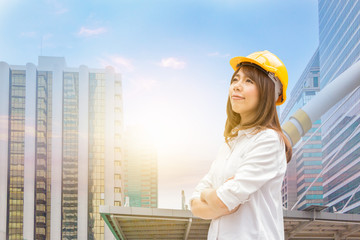 Construction and maintenance Think Big concept, Female architect in yellow helmet with city background