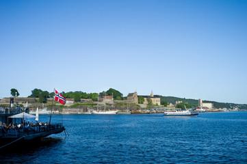 Oslo harbour. Aker Brygge. Boats near Akershus Castle. Norwegian flag