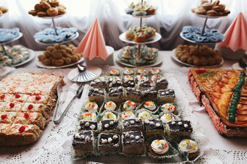 Tasty pieces of different cakes with chocolate and fruits stand