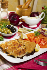 Breaded and deep fried hake fillets on a white plate with lemon, tomatoes and potato salad served next to fresh vegetables, olives, olive oil and sauce.