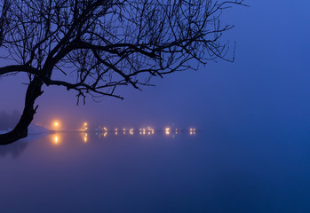 Lights on a molo reflected in the sea water. Misty evening.