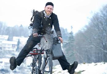 Schornsteinfeger fährt mit Fahrrad durch Winterlandschaft
