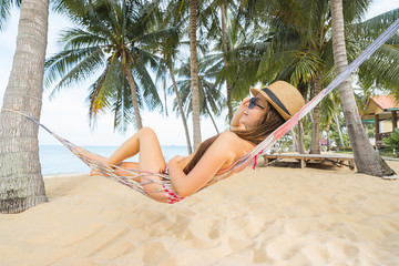 Vacation concept. Young happy woman in hat and sunglasses laying in hammock on the beach.
