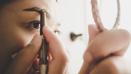 Woman drawing her eyebrow.