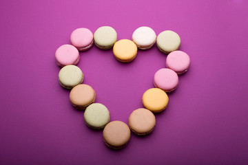 Heart shape made of colorful macaroons or macarons dessert on purple background