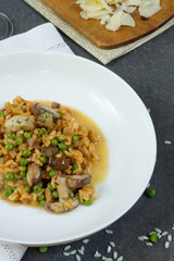 Risotto with mushrooms and green peas. White plate, gray background, glass of wine.