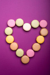 Heart shape made of colorful macaroon or macaron dessert on purple background
