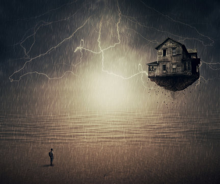 Surreal background of a man standing in the rain, in front of a flying house ripped from the ground, near the ocean. Sixth sense concept.