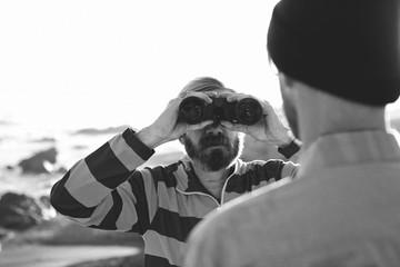 Man looking at another man through binoculars, black and white