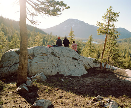 People sitting on large rock in forest with mountains