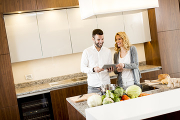 Young couple looking tatablet in the kitchen while preparing mea