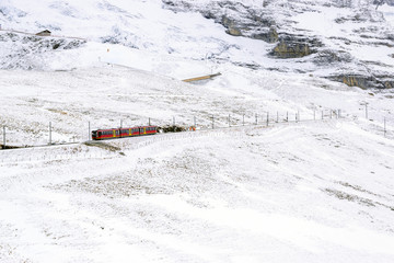 Passenger train in winter with snow on the mountains in Switzerland.