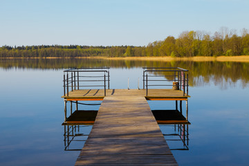 Wooden pier on the lake. Sunny morning.