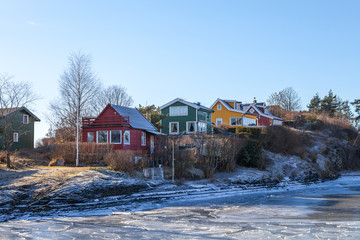 Color wooden cabins on the island with frozen sea at the foreground. Scandinavian style