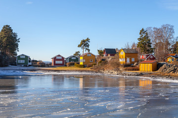 Color wooden cabins on the island with frozen sea at the foreground. Scandinavian style. Sunny winter day