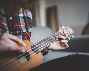 Cropped imge of young teen hipster girl playing ukulele guitar at cozy home interior, filtered image, film effects, positive mood
