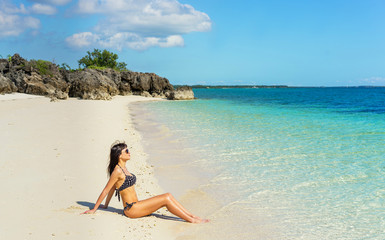 Young girl in black swimwear enjoying  sunny day on the beach.