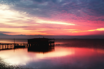 Long exposure of magic sunrise over the ocean with a hut in the