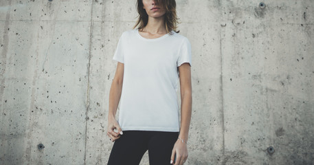 Pretty young fit girl wearing blank white t-shirt with copy space for your logo or design, mock-up of template t-shirt, concrete grey wall in the background