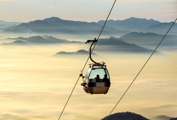Sight on the cable-way infrastructure over foggy valley. Ropeway and cablecar transport system for skiers