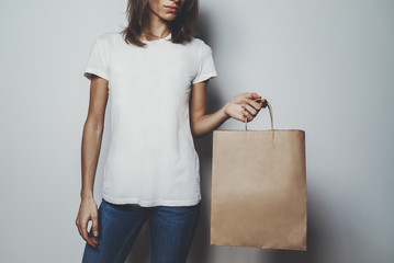 Young hipster girl wearing blank white t-shirt and holding brown craft package with empty space for your logo or design, mock-up of white cotton t-shirt and shopping bag with handles