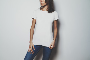 Young hipster girl wearing blue jeans and blank white t-shirt with empty area for your logo or design, mock-up of white cotton t-shirt, white wall in the backround