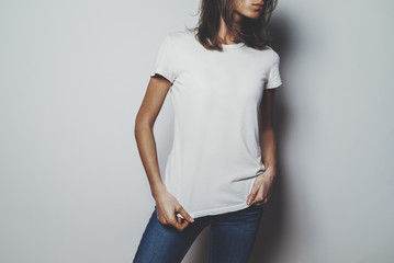 Young hipster girl wearing blue jeans and white blank t-shirt with space for your logo or design, mock-up of white cotton t-shirt, white wall in the background