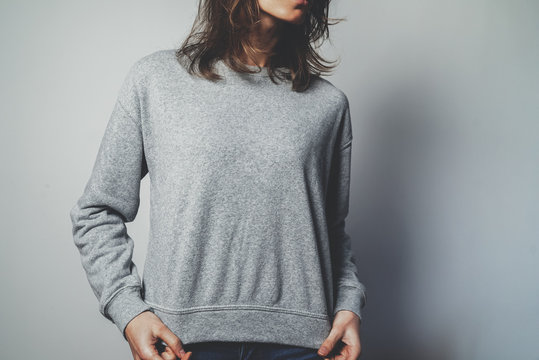 Young hipster girl wearing blank grey cotton sweatshirt with copy space for your design or logo, mock-up of grey template women's hoodie, white wall in the background