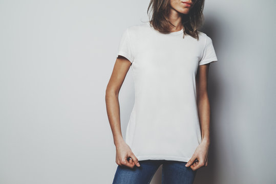 Young hipster girl wearing blue jeans and blank white t-shirt with area for your logo or design, mock-up of white t-shirt, white wall in the background