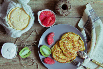 Pancakes on a large gray plate, fruit and dairy products. Country style