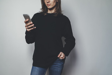 Young pretty girl using modern smartphone device and wearing blank oversize hoodie with space for logo or design, mock-up of black women's sweatshirt, white wall in the background