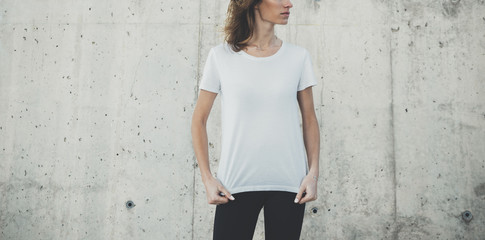 Young pretty girl wearing blank white t-shirt with space for your logo, concrete wall in the background with copy space for your content or design, mock-up of template white t-shirt