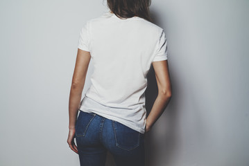 Mock-up of white t-shirt, young hipster girl wearing blue jeans and blank white t-shirt, back view, white wall in the background