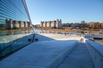 View on a side of the National Oslo Opera House with city reflected in glass