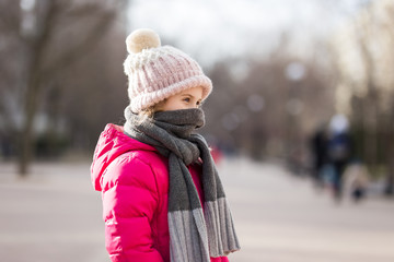 Closeup portrait of cute baby girl wearing knitted hat and winter jacket outdoors