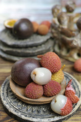 Lychees and Passion Fruit or Maracuya on wooden background - exotic fruits