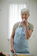 Cheerful mature woman enjoys snacking on a piece of fresh vegetable as she prepares a healthy lunch.