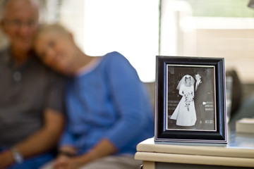 Happy senior couple sitting behind a framed photo of a young couple on their wedding day.