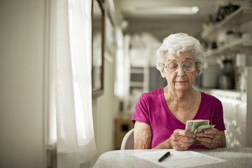 Senior woman counting money while sitting at home