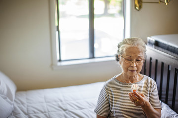 Elderly woman reads the instructions on her bottle of medication.
