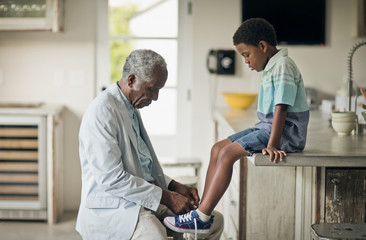 Grandfather tying shoelace of his grandson at kitchen